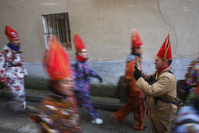 """A believer uses a tablet computer to record other """"diablos"""" parading around town during the """"Endiablada"""" festival in Almonacid del Marquesado, in central Spain February 3, 2015. (Photo by Susana Vera/Reuters)"""