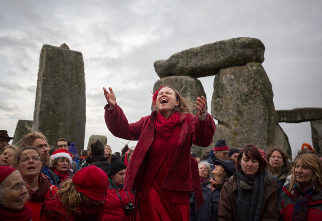 Susie Ro Prater (C) leads the Shakti Sings choir as druids, pagans and revellers gather in the centre of Stonehenge, hoping to see the sun rise, as they take part in a winter solstice ceremony at the ancient neolithic monument of Stonehenge near Amesbury on December 22, 2015 in Wiltshire, England. (Photo by Matt Cardy/Getty Images)