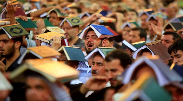 Shi'ite pilgrims place copies of the Koran on their heads during the ceremony marking the anniversary of the death of Imam Ali at his shrine in the holy city of Najaf, on July 30, 2013. (Photo by Ahmad Mousa/Reuters)
