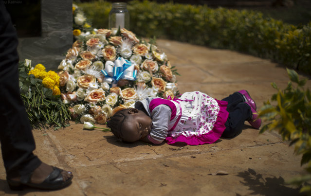 Nicole Tashly, 2, lies quietly on the ground holding the white rose her mother Esther Muthoni, left, instructed her to lay at the memorial monument while they remember her father Paul Muriithi Muriuki who died in the Westgate Mall attack, as they and other families of the victims lay flowers and remember, at the Amani Garden memorial site in the Karura Forest in Nairobi, Kenya Sunday, September 21, 2014. (Photo by Ben Curtis/AP Photo)