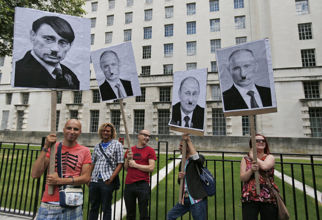 "Activists holding placards depicting Russian President Vladimir Putin as Adolf Hitler, participate at a protest against Russia's new law on gays, in central London, Saturday, August 10, 2013. Hundreds of protesters, called for the Winter 2014 Olympic Games to be taken away from Sochi, Russia, because of a new Russian law that bans ""propaganda of nontraditional sexual relations"" and imposes fines on those holding gay pride rallies. (Photo by Lefteris Pitarakis/AP Photo)"
