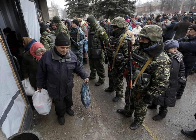 Local residents carry bags of humanitarian aid next to Ukrainian servicemen in Debaltseve, eastern Ukraine, February 6, 2015. (Photo by Gleb Garanich/Reuters)