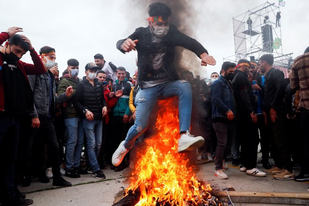 A person jumps over a bonfire as people gather to celebrate Newroz, which marks the arrival of spring, in Istanbul, Turkey on March 20, 2021. (Photo by Murad Sezer/Reuters)
