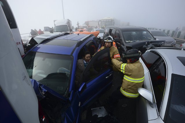 Firefighters rescue a flight attendant from a damaged vehicle on Yeongjong Bridge in Incheon February 11, 2015. (Photo by Park Jung-ho/Reuters/News1)