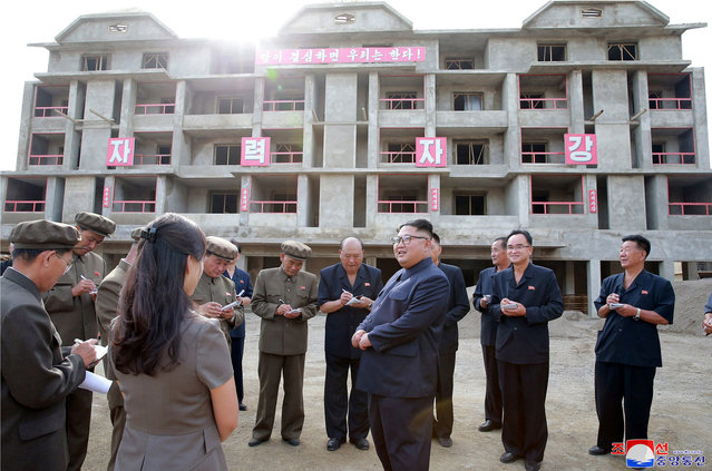 """In this undated photo, provided on August 19, 2018, by the North Korean government, North Korean leader Kim Jong Un, center, visits a construction site during a visit to the city of Samjiyon, a remote northern city near the Chinese border.  North Korea is speeding up the pace of a massive nationwide construction campaign ahead of its 70th anniversary in what leader Kim has described as a symbolic battle against anyone who would oppose his country. Independent journalists were not given access to cover the event depicted in this image distributed by the North Korean government. The content of this image is as provided and cannot be independently verified. Korean language watermark on image as provided by source reads: """"KCNA"""" which is the abbreviation for Korean Central News Agency. (Photo by Korean Central News Agency/Korea News Service via AP Photo)"""