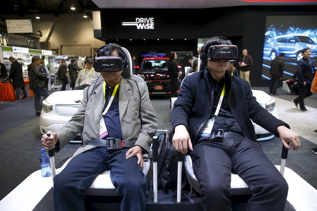 Attendees sit in a virtual reality simulator as they watch a VR movie featuring an autonomous Kia Soul at the Kia booth during the 2016 CES trade show in Las Vegas, Nevada January 8, 2016. (Photo by Steve Marcus/Reuters)