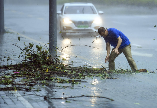 In this photo released by Xinhua News Agency, a man removes debris blocking a drain on a road at Nanshan District in Shenzhen in south China's Guangdong Province, Sunday September 16, 2018. Typhoon Mangkhut barrelled into southern China on Sunday after lashing the northern Philippines with strong winds and heavy rain that left at least 64 people dead and dozens more feared buried in a landslide. (Photo by Mao Siqian/Xinhua via AP Photo)