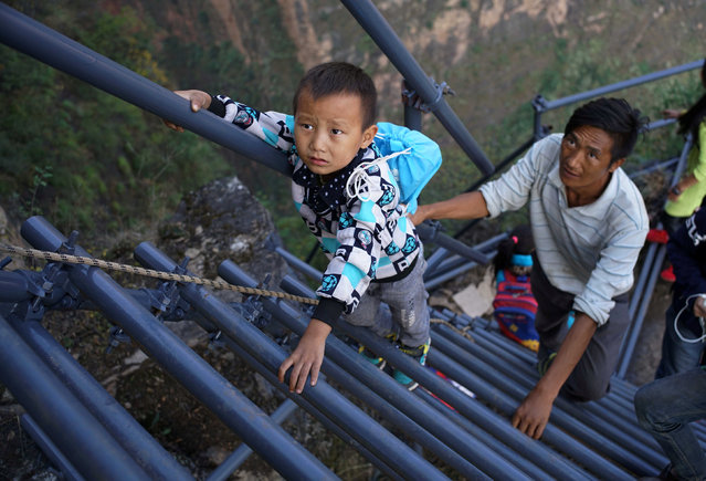 "A student from ""the cliff village"" in Atule'er climbs newly-constructed steel ladders after school to go home for holidays, in Liangshan Sichuan province, China, November 19, 2016. The steel ladders which replaced the unsafe vine ladders shortened the time taken for the children to go home, from three hours to two. (Photo by Reuters/Stringer)"