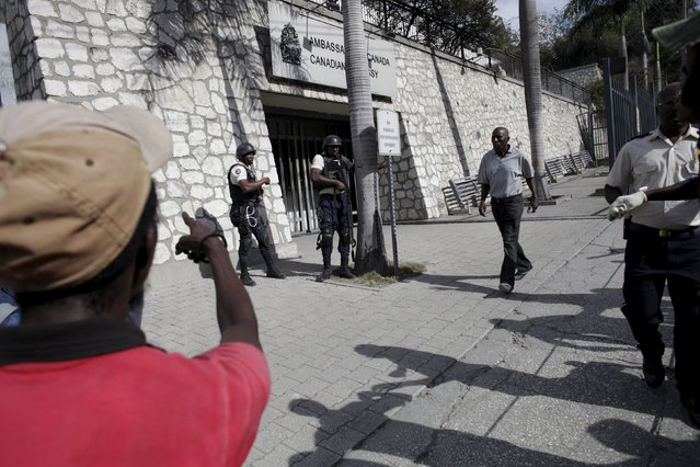 A resident walks in front of protesters arguing with National Police officers standing guard the Canadian Embassy during a demonstration against the electoral process in Port-au-Prince, Haiti, January 22, 2016. (Photo by Andres Martinez Casares/Reuters)