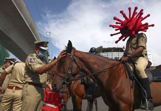 A policeman rides a horse wearing a virus-themed helmet during a COVID-19 awareness drive in Hyderabad, India, Tuesday, June 1, 2021. (Photo by Mahesh Kumar A./AP Photo)