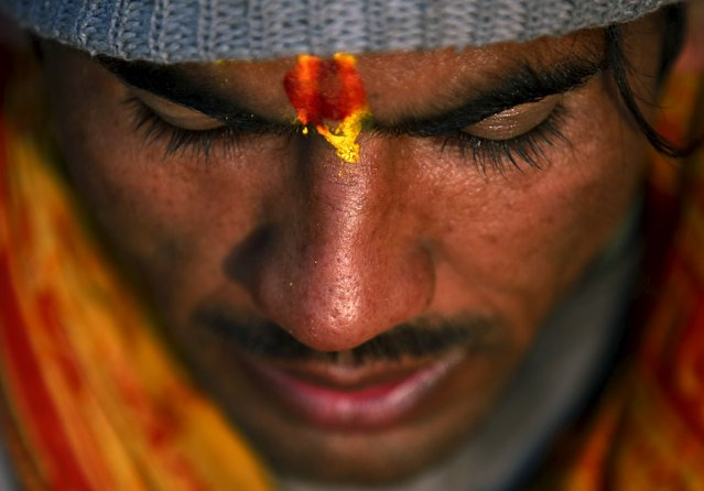 A Hindu holy man recites verses from the holy Swasthani Brata Katha book at the bank of River Saali in Sankhu during the Swasthani Brata Katha festival in Kathmandu, Nepal, January 24, 2016. (Photo by Navesh Chitrakar/Reuters)