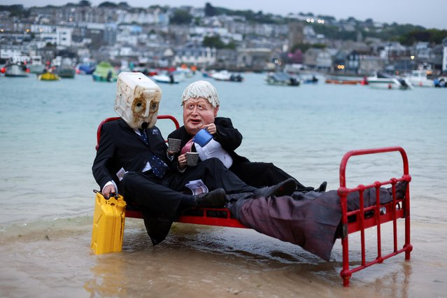 Activists from climate action group Ocean Rebellion demonstrate in St Ives Harbour, ahead of the G7 summit, in St Ives, Cornwall, Britain, June 9, 2021. (Photo by Tom Nicholson/Reuters)