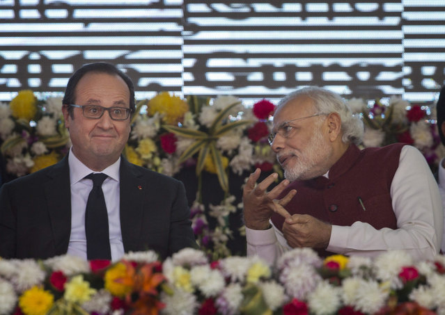 French President Francois Hollande, left, and Indian Prime Minister Narendra Modi interact during the foundation stone laying for the headquarters of the International Solar Alliance at Gurgaon, outskirts of New Delhi, India, Monday, January 25, 2016. The solar energy alliance was launched last month during global climate talks held in Paris. Hollande is on a three-day visit to India. (Photo by Saurabh Das/AP Photo)