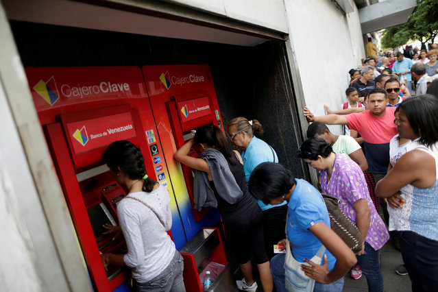 People line up to withdraw cash from an automated teller machine (ATM) outside a Banco de Venezuela branch in Caracas, Venezuela, December 5, 2016. (Photo by Ueslei Marcelino/Reuters)