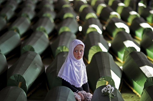 A girl sits next to a coffin of her relative, one of the 173 coffins of newly identified victims from the 1995 Srebrenica massacre, in the Potocari Memorial Center, near Srebrenica in this July 9, 2014 file photo. Serbia arrested seven men on March 18, 2015 suspected of taking part in the 1995 Srebrenica massacre in Bosnia, the first such arrests in the ex-Yugoslav republic of accused gunmen in Europe's worst atrocity since World War Two. (Photo by Dado Ruvic/Reuters)