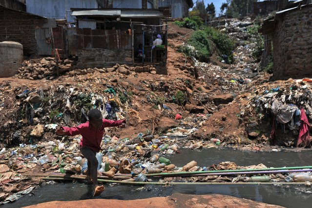A young resident of Nairobi's Kibera slum, one of Africa's largest slums, crosses a heavily polluted section of the Ngong river on September 19, 2018. (Photo by Tony Karumba/AFP Photo)