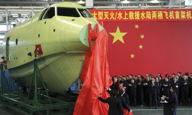 Officials of Aviation Industry Corporation of China (AVIC) unveil the newly-made nose of amphibious aircraft AG600, during a ceremony at a factory in Chengdu, Sichuan province March 17, 2015. The Chinese self-developed amphibious aircraft will have its maiden flight in 2016 as the production of its nose was completed on Tuesday in southwest China's Sichuan Province, according to a staff with the AVIC. (Photo by Reuters/China Daily)