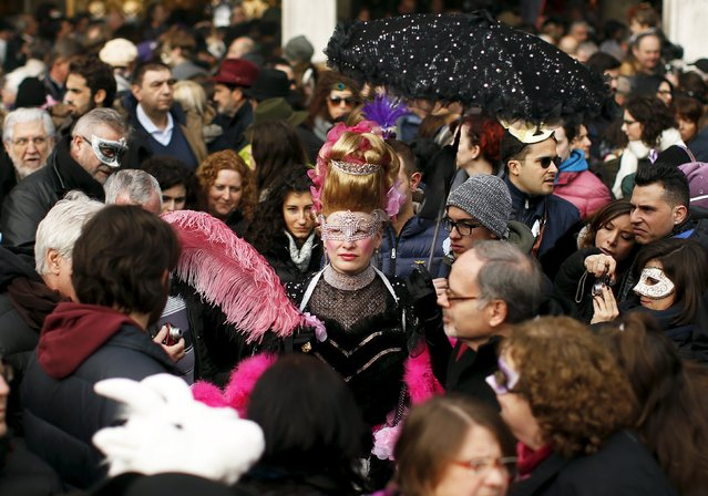 A reveller (C) watches as the traditional Columbine descends from Saint Mark's tower bell on an iron cable during the Venice Carnival, January 31, 2016. (Photo by Alessandro Bianchi/Reuters)