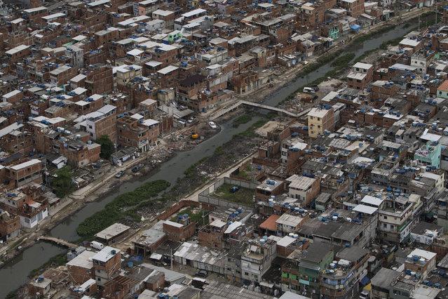 A polluted channel runs through the Rio das Pedras shantytown in Rio de Janeiro, Brazil, Monday, March 23, 2015. (Photo by Felipe Dana/AP Photo)
