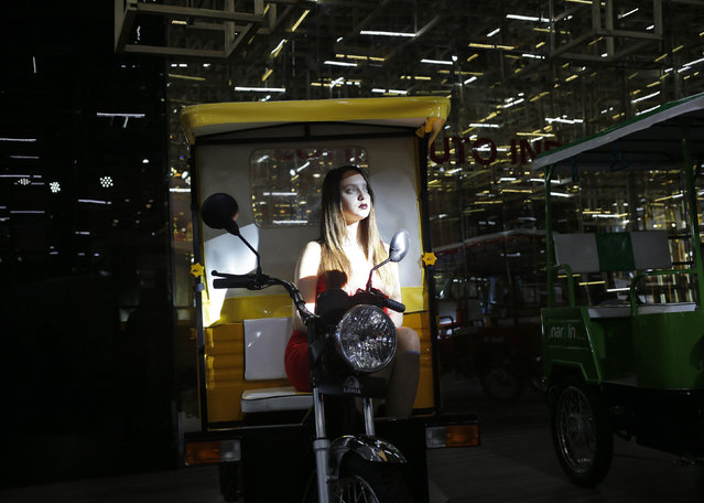 A model poses as she sits in a Lohia auto-rickshaw at the Indian Auto Expo in Greater Noida, on the outskirts of New Delhi, India, February 4, 2016. (Photo by Anindito Mukherjee/Reuters)
