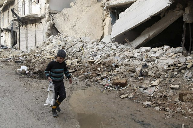 A boy walks holding a rabbit beside damaged buildings in Aleppo December 31, 2014. Picture taken December 31, 2014. (Photo by Hamid Khatib/Reuters)