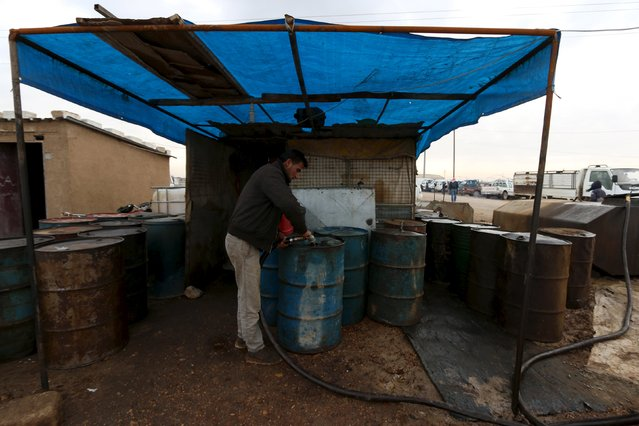 A man fills drums with oil for sale at the Syrian town of Ras al-Ain, close to the Turkish border, January 23, 2016. (Photo by Rodi Said/Reuters)