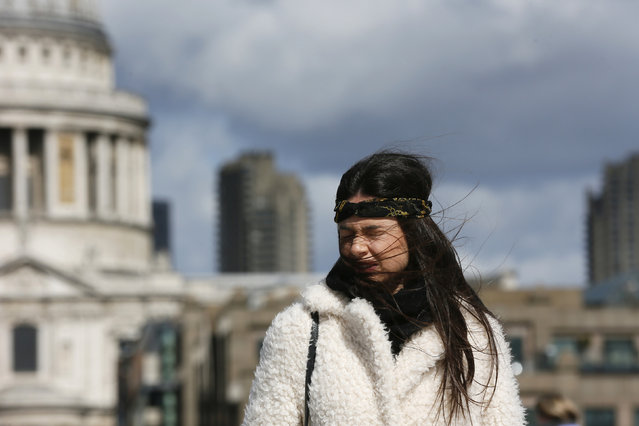 A young woman reacts as she crosses the Millennium Bridge during strong winds in London, March 31, 2015. (Photo by Stefan Wermuth/Reuters)