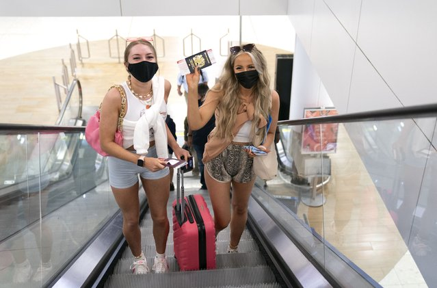 Friends Poppy (left) and Shannon, both aged 20 and from Glasgow, head towards the departure gate at Glasgow Airport after checking in for their flight to Ibiza on Monday, July 19, 2021. (Photo by Jane Barlow/PA Images via Getty Images)
