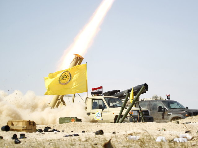 Shi'ite paramilitary fighters launch a rocket towards Islamic State militants in Tikrit March 31, 2015. (Photo by Alaa Al-Marjani/Reuters)