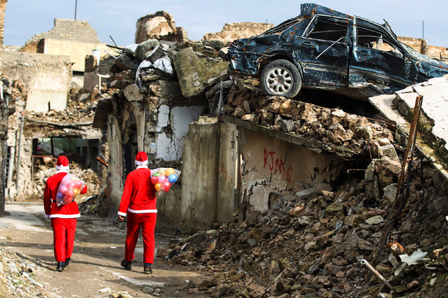 Iraqi youths dressed in Father Christmas suits walk through the streets of the old city of Mosul as they distribute gifts, on December 26, 2018. Iraq on December 10 marked the first anniversary since declaring victory in its three-year war against the Islamic State (IS) group, which had left the country's former second city and the jihadists' capital in ruin. (Photo by Ahmad Al-Rubaye/AFP Photo)