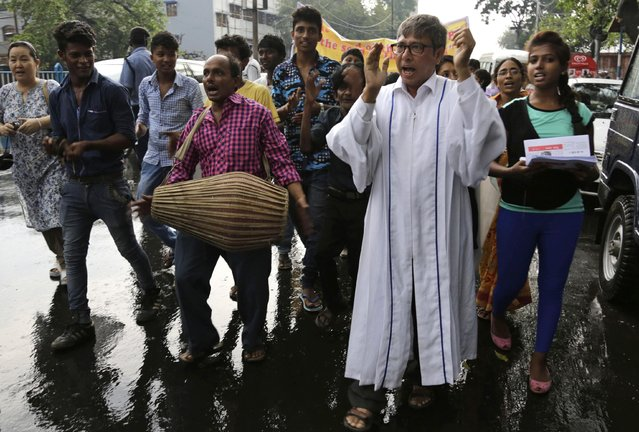 A Catholic priest sings as Indian Christians walk in the rain during an Easter procession in Kolkata, India, Sunday, April 5, 2015. Christians around the world are celebrating Easter commemorating the day when according to Christian tradition Jesus was resurrected in Jerusalem two millennia ago. (Photo by Bikas Das/AP Photo)