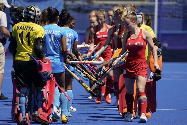 Members of the India team, left, greet members of the Britain team prior to their women's field hockey bronze medal match at the 2020 Summer Olympics, Friday, August 6, 2021, in Tokyo, Japan. (Photo by John Locher/AP Photo)