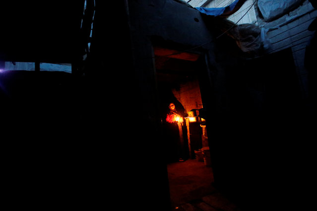 A Palestinian woman uses a candle light as she works in her kitchen during a power cut inside her house in Beit Lahiya in the northern Gaza Strip January 11, 2017. (Photo by Mohammed Salem/Reuters)