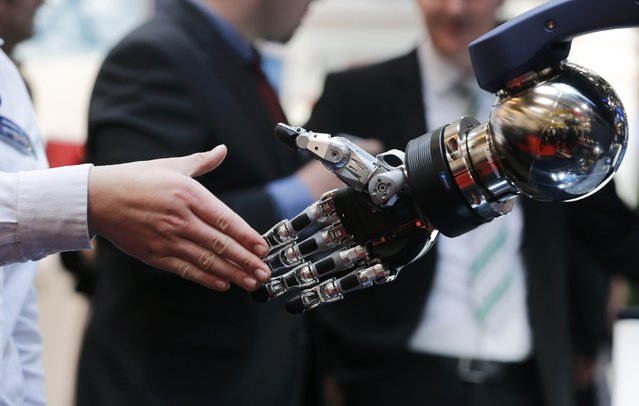A woman reaches out to shake hands with a robotic hand at the booth of Schunk at the world's largest industrial technology fair, the Hannover Messe, in Hanover April 13, 2015. (Photo by Wolfgang Rattay/Reuters)