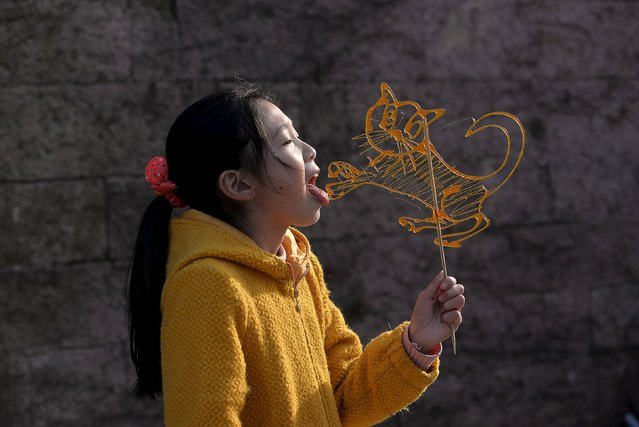 A girl licks a traditional candy in the shape of a tiger at a folk art exhibition celebrating the Lantern Festival in Ningbo, Zhejiang Province, China, February 20, 2016. (Photo by Reuters/Stringer)