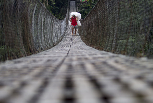 A Nepalese farmer carries a bundle containing his agriculture products as he crosses the Trishul river on a suspension bridge in the Dhading District, some 90 kilometers from the capital Kathmandu, Nepal, April 13, 2015. (Photo by Narendra Shrestha/EPA)