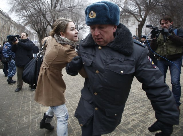 Police officers detain people who gathered for an unsanctioned event in downtown Volgograd, Russia, Monday, December 30, 2013. A bomb blast tore through a trolleybus in the city of Volgograd on Monday morning, killing at least 10 people. a day after a suicide bombing that killed at least 17 at the city's main railway station. Volgograd is about 650 kilometers (400 miles) northeast of Sochi, where the Olympics are to be held. (Photo by Denis Tyrin/AP Photo)