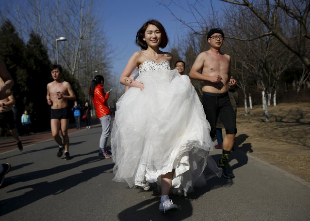 "A woman wearing a wedding dress runs at the ""Half-Naked Marathon"" at Olympic Forest park in Beijing, China, February 28, 2016 (Photo by Kim Kyung-Hoon/Reuters)"