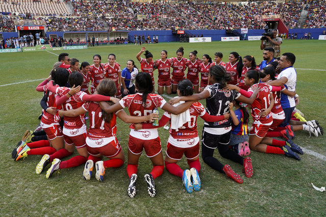 Salcomp players huddle at the center of the pitch of Arena da Amazonia after winning the Peladao amateur soccer tournament in Manaus, Brazil, Saturday, February 16, 2019. It is the team's second title, the first was in 2011. (Photo by Victor R. Caivano/AP Photo)