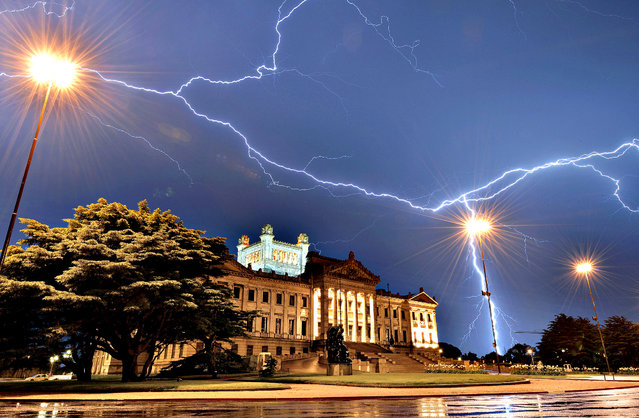 Lightning streaks across the sky of Montevideo, over the Legislative Palace – seat of the Uruguayan Government – during a thunderstorm early on January 10, 2014. (Photo by Mariana Suarez/AFP Photo)