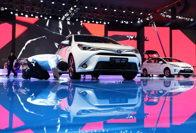 A worker looks at a Toyota Motor Corp. Levin hybrid electric vehicle, left, at the 16th Shanghai International Automobile Industry Exhibition (Auto Shanghai 2015) in Shanghai, China, on Monday, April 20, 2015. (Photo by Tomohiro Ohsumi/Bloomberg)