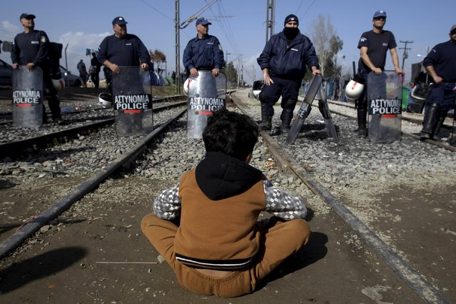A refugee sits in front of a Greek riot police cordon during a protest at the Greek-Macedonian border, near the Greek village of Idomeni, March 1, 2016. (Photo by Alexandros Avramidis/Reuters)