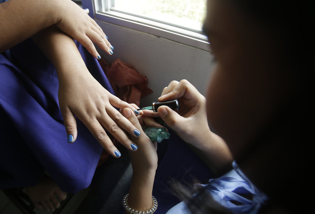 In this January 6, 2017 photo, a transgender inmate, right, paints another's nails during a lesson at Pattaya Remand Prison in Pattaya, Chonburi province, Thailand. (Photo by Sakchai Lalit/AP Photo)