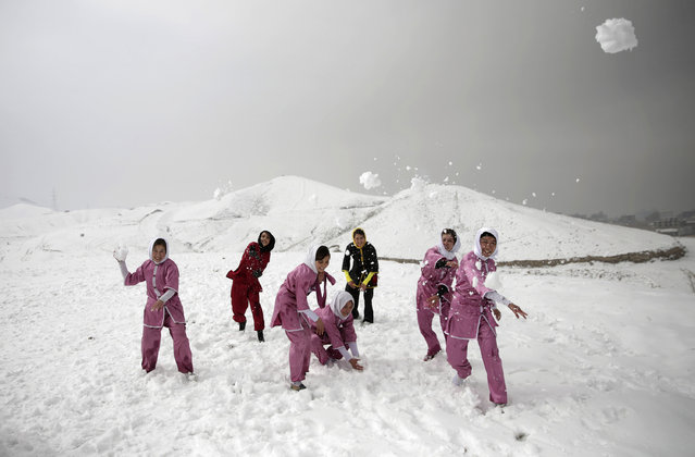 Shaolin martial arts students and their trainer have a snowball fight after their training session in Kabul, Afghanistan, Tuesday, January 25, 2017. The ten ethnic Hazara women and girls practice the martial arts of Shaolin on a hilltop in the west of Kabul. (Photo by Massoud Hossaini/AP Photos)