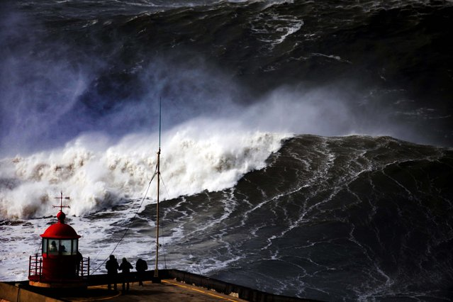 People watch huge waves approach the Nazare lighthouse, outside the fishing village of Nazare, Portugal, on February 2, 2014. According to the Portuguese weather institute, waves above 18 feet high were expected to hit the coastline and a few ports, most of them in the north of the country, were closed due to the rough sea. (Photo by Francisco Seco/Associated Press)