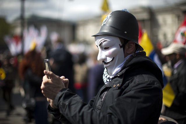 A protester wearing a toy British police helmet and an Anonymous mask takes a picture during a rally at the end of a May Day demonstration march in Trafalgar Square in London, Friday, May 1, 2015. Tens of thousands of workers marked May Day in European cities with a mix of anger and gloom over austerity measures imposed by leaders trying to contain the eurozone's intractable debt crisis. (Photo by Matt Dunham/AP Photo)