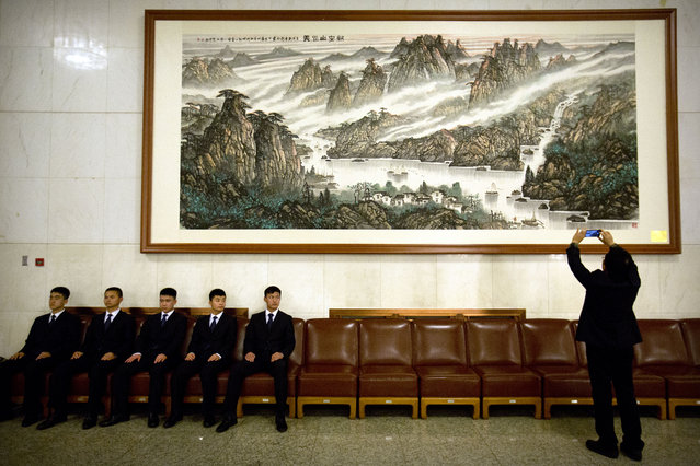 Security personnel watch as a man takes a photo of a painting inside the Great Hall of the People before the start of the closing session of the Chinese People's Political Consultative Conference (CPPCC) in Beijing, Monday, March 14, 2016. (Photo by Mark Schiefelbein/AP Photo)