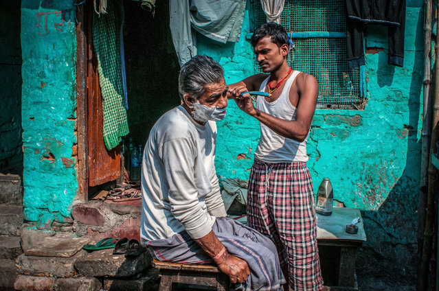 """Wandering round the Potter's Town area of Kolkata, I was fascinated by all the activities taking place in the side streets. The brightly coloured walls were the perfect backdrop to this outdoor shave"". PAUL GOLDSTEIN, JUDGE: ""I thought I was immune to these sort of candid sub-continent images – clearly not when done this well. It is neither intrusive nor cliched but is not arrived at by accident. The gorgeous colours cover most of the blue through turquoise Pantone chart. However, it is the utter indifference on the expressions that caps it for me"". (Photo by Louise Waldron/The Guardian)"
