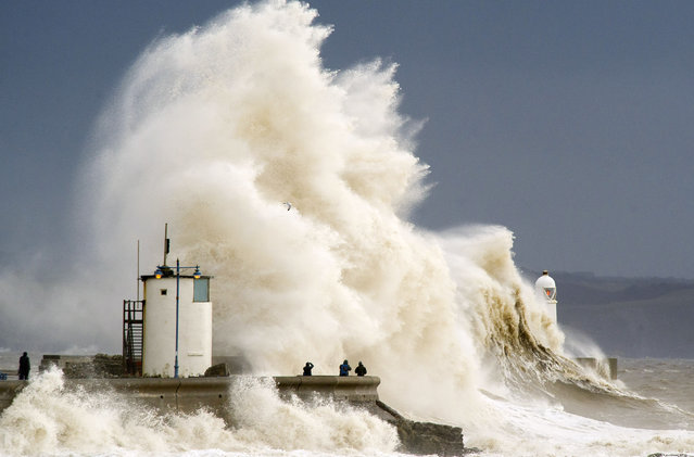 Spectators watch as waves break over the harbour wall at Porthcawl during a high tide on February 5, 2014 in Porthcawl, United Kingdom. High tides combined with gale force winds and further heavy rain mean some parts of the UK are bracing themselves for more flooding. (Photo by Matthew Horwood/Getty Images)