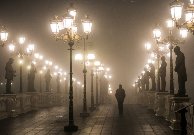 A man walks over a bridge through dense fog and smog in Skopje late on December 22, 2018. Skopje was named Europe's most polluted capital in 2018 by the World Health Organization, partly because two-thirds of households use firewood as their primary source of heating. (Photo by Robert Atanasovski/AFP Photo)